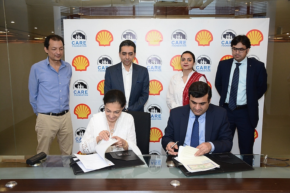Haroon Rashid and Seema Aziz signing papers