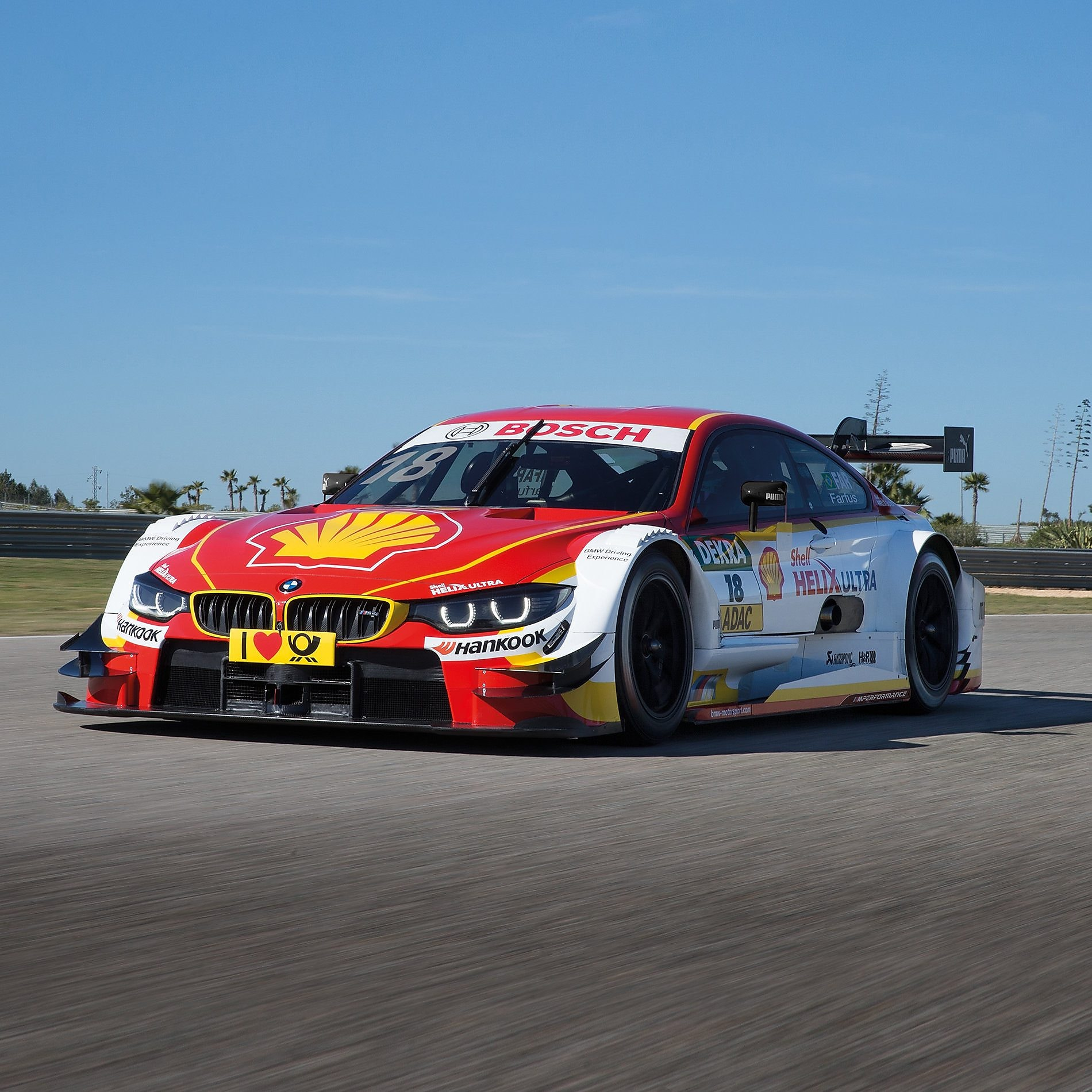 A red and white BMW race car sits on the track, exemplifying the Shell Helix Ultra and BMW's Premium Technology Partnership